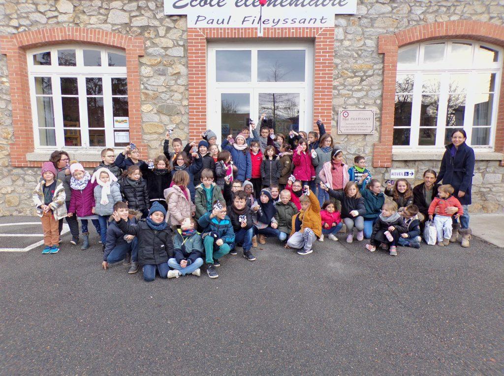Les CP et les CM1 réunis devant l'école pour présenter les tawashis fabriqués ensemble.